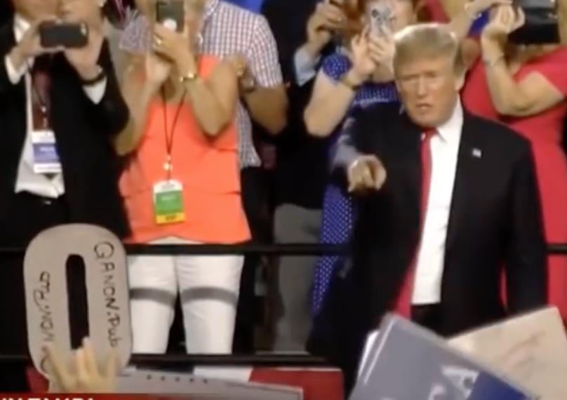 Trump zeigt auf ausgeschnittenes Q-Symbol