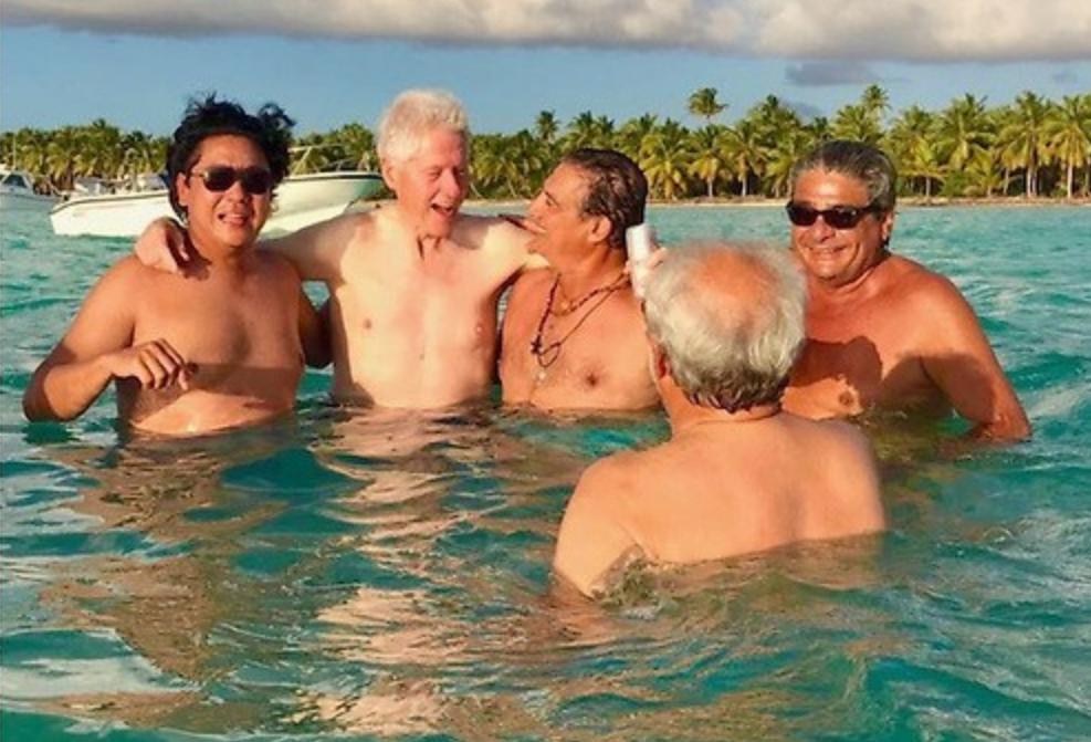 """Ricardo Cheaz, Bill Clinton, George Nader, José Calzada, Rolando Gonzalez Bunster baden vor einer """"unbekannten"""" Insel"""